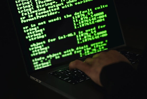 Green Code on Laptop Screen with Hand on Keyboard
